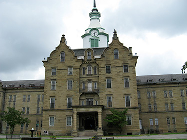 The imposing entrance. Note the restored clock tower on top. It only has clock faces on three sides; the fourth faced the direction of the fields some inmates worked in order to supply the asylum with food. Without  a clock, they had no way of knowing how long they had been working, other than the change in sunlight.
